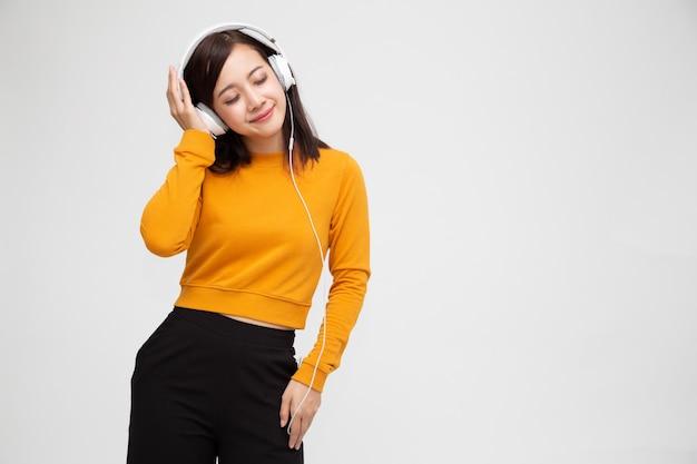 Mooie jonge aziatische vrouw die met hoofdtelefoons aan muziek in heldere uitrusting luistert die van de geïsoleerde liedmelodie geniet