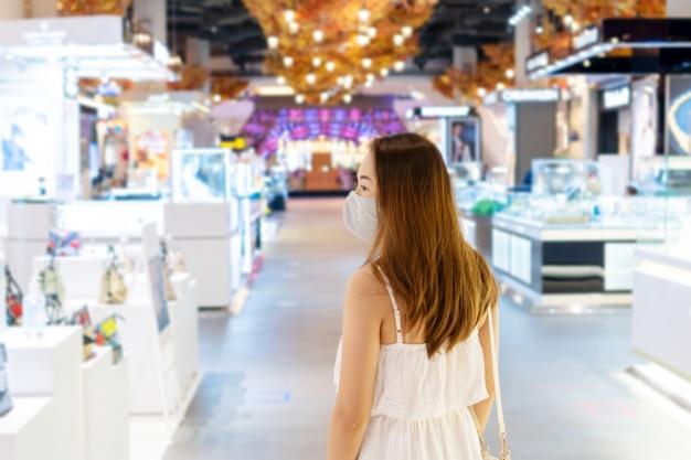 Mooie jonge aziatische vrouw die met ptotective gezichtsmasker bij winkelcentrum of warenhuis loopt