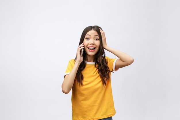 Mooie jonge aziatische vrouw die mobiele telefoon en glimlach spreekt