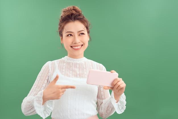 Mooie jonge aziatische vrouw die mobiele telefoon toont terwijl ze staat en omhoog kijkt geïsoleerd over groene achtergrond.