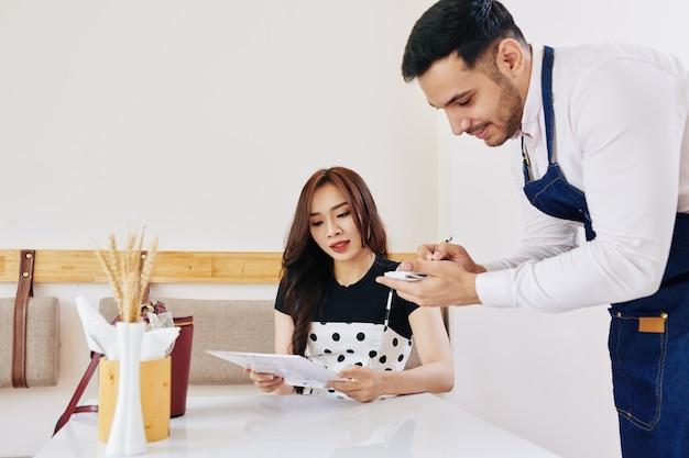 Mooie jonge aziatische vrouw die ober over schotelingrediënten vraagt bij het maken van orde in koffie