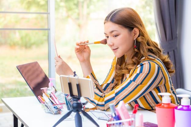 Mooie jonge aziatische vrouw die online productoverzicht thuis maakt