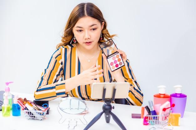 Mooie jonge aziatische vrouw die online productoverzicht thuis maken