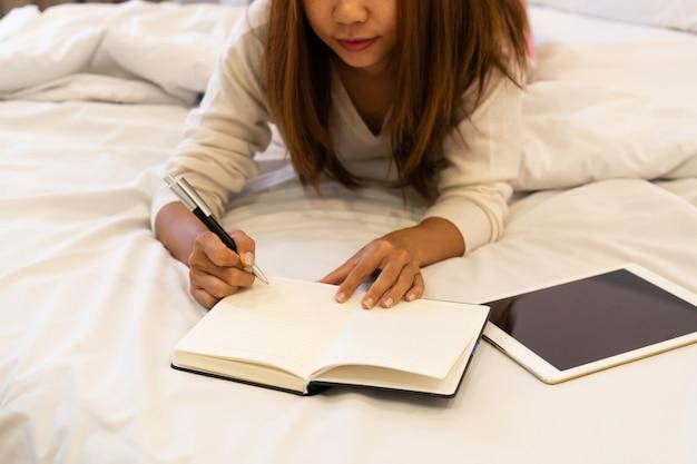 Mooie jonge aziatische vrouw die op bed legt en een agenda schrijft. glimlachende donkerbruine dame met notitieboekje en pen in haar handen met opzij gezette tablet. modern licht interieur op de achtergrond.