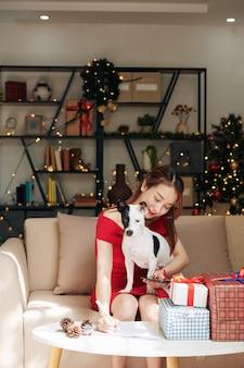 Mooie jonge aziatische vrouw die op de bank zit met een schattige kleine hond op haar schoot en een kerstcadeaulijst maakt