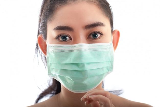 Mooie jonge aziatische vrouw die op een medisch masker zetten om tegen covid-19 te beschermen