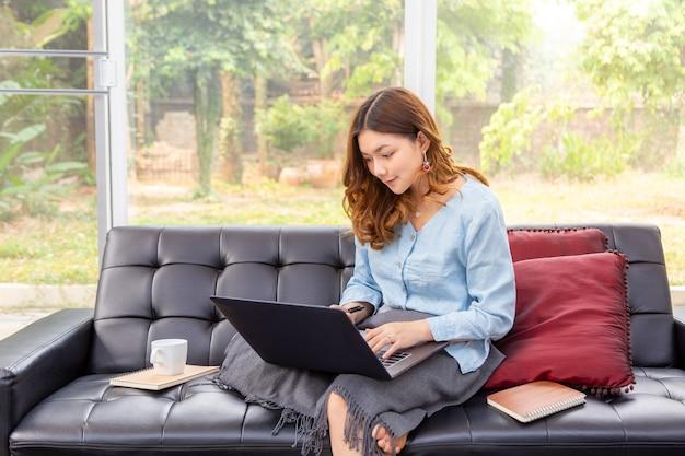 Mooie jonge aziatische vrouw die op haar computer in haar woonkamer thuis met haar achtertuin werkt