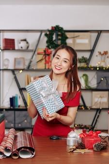 Mooie jonge aziatische vrouw die poseert met een groot kerstcadeau dat ze inpakte voor de beste vriend