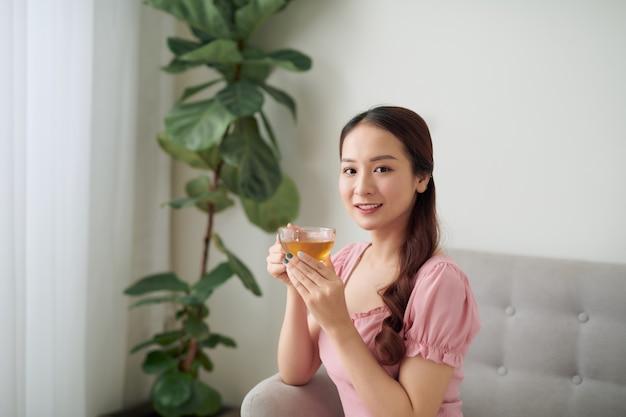 Mooie jonge aziatische vrouw die 's ochtends thee drinkt in de woonkamer.