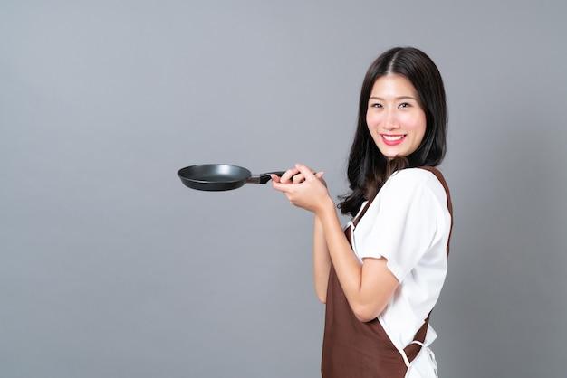 Mooie jonge aziatische vrouw die schort met hand draagt die zwarte pan op grijs houdt