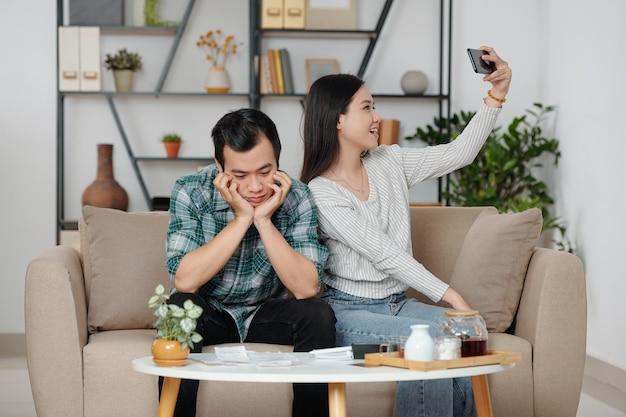 Mooie jonge aziatische vrouw die selfie neemt wanneer haar trieste, gestresste vriend kijkt naar een stapel energierekeningen, belastingdocumenten en creditcardrekeningen die voor hem liggen