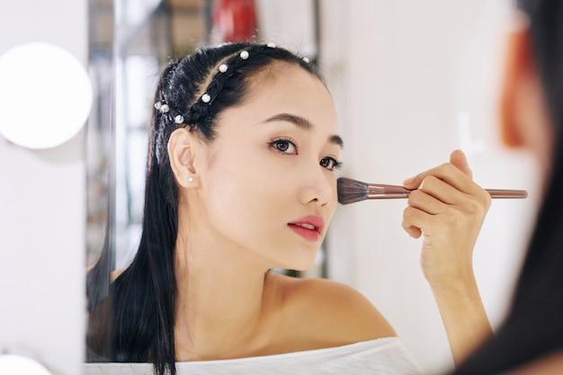 Mooie jonge aziatische vrouw die spiegel bekijkt en losse gezichtspoeder op haar wangen toepast