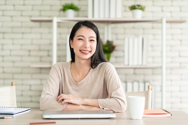 Mooie jonge aziatische vrouw die vanuit huis werkt en zich gelukkig voelt lachend met een vrolijke uitdrukking