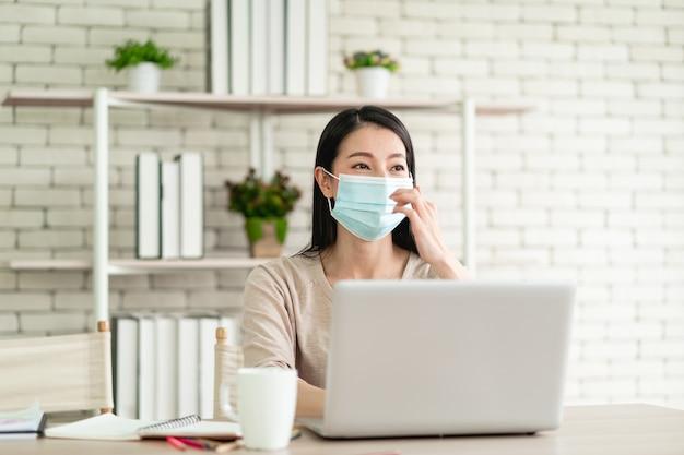 Mooie jonge aziatische vrouw draagt een chirurgisch masker dat vanuit huis werkt en zich gelukkig voelt met een blije uitdrukking
