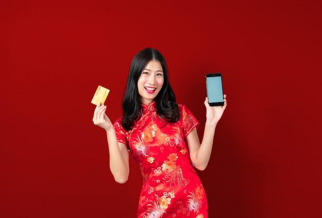 Mooie jonge aziatische vrouw draagt rode chinese jurk met behulp van smartphone en creditcard op rood te houden