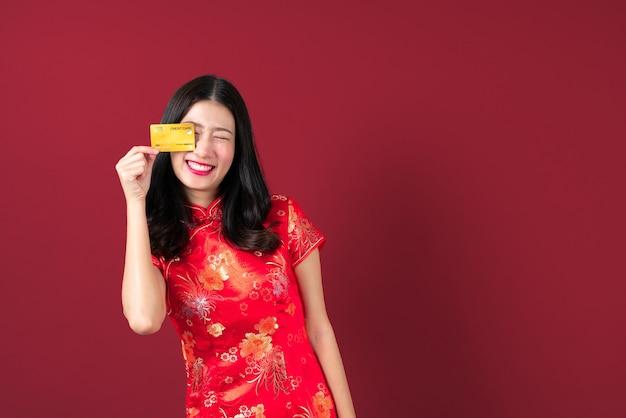 Mooie jonge aziatische vrouw draagt rode chinese traditionele kleding met de creditcard van de handholding om vertrouwen en vertrouwen te tonen voor het doen van betaling op grijs