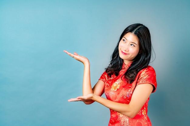 Mooie jonge aziatische vrouw draagt rode chinese traditionele kleding met hand die aan kant in blauw presenteert
