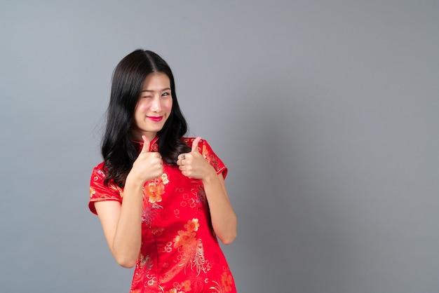 Mooie jonge aziatische vrouw draagt ?? rode chinese traditionele kleding met hand presenteren aan de zijkant in grijs
