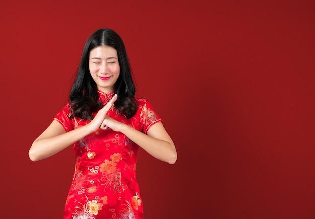 Mooie jonge aziatische vrouw draagt ?? rode chinese traditionele kleding met hand presenteren aan kant