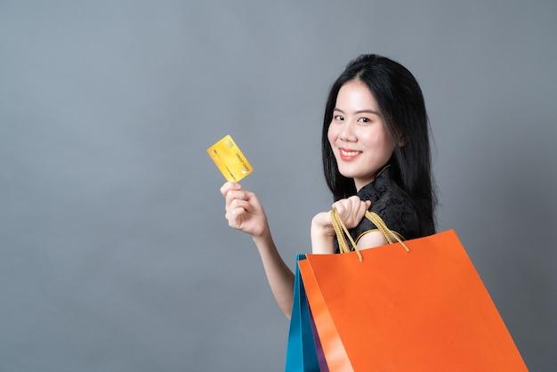 Mooie jonge aziatische vrouw draagt traditionele chinese kleding met boodschappentas en creditcard op grijs oppervlak