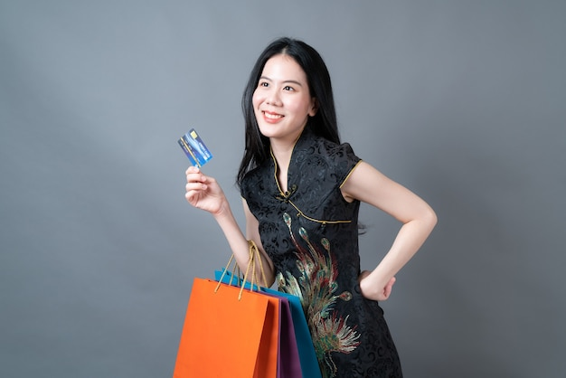 Mooie jonge aziatische vrouw draagt traditionele chinese kleding met boodschappentas en creditcard op grijze muur