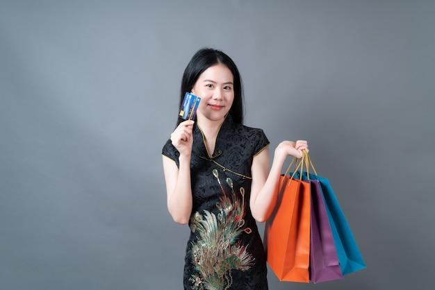 Mooie jonge aziatische vrouw draagt traditionele chinese kleding met boodschappentas en creditcard