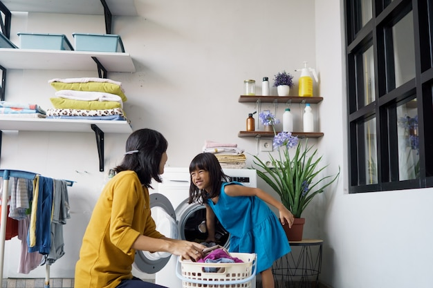 Mooie jonge aziatische vrouw en kind meisje weinig helper doen thuis was.