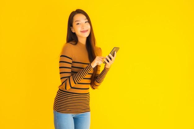 Mooie jonge aziatische vrouw gebruik slimme mobiele telefoon of mobiel met veel actie op gele achtergrond