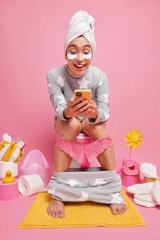 Mooie jonge aziatische vrouw gekleed in nachtkleding past schoonheidspatches toe en gebruikt mobiele telefoon terwijl ze op het toilet zit en een handdoek over het hoofd gewikkeld draagt geïsoleerd over roze muur