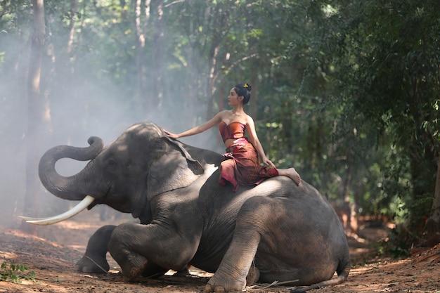 Mooie jonge aziatische vrouw gekleed in traditionele inheemse kleding en olifant in bos van dorp su