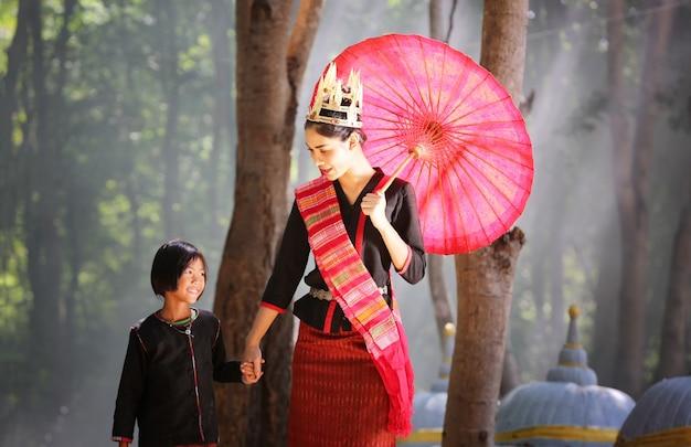Mooie jonge aziatische vrouw gekleed in traditionele inheemse kleding en olifant in bos van dorp
