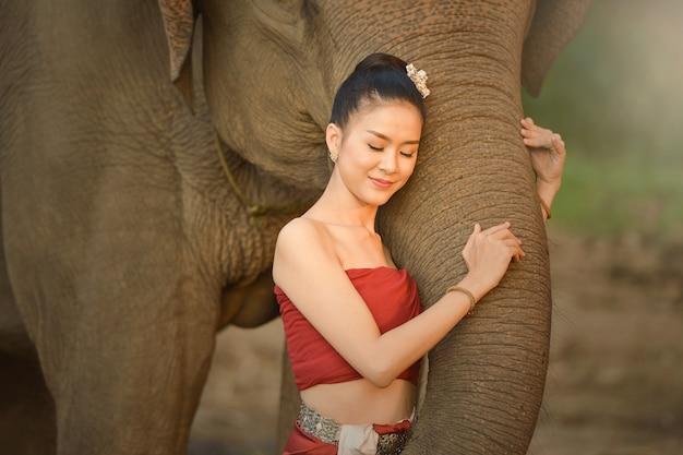 Mooie jonge aziatische vrouw gekleed in traditionele inheemse kleding en olifant in het bos van het dorp surin thailand