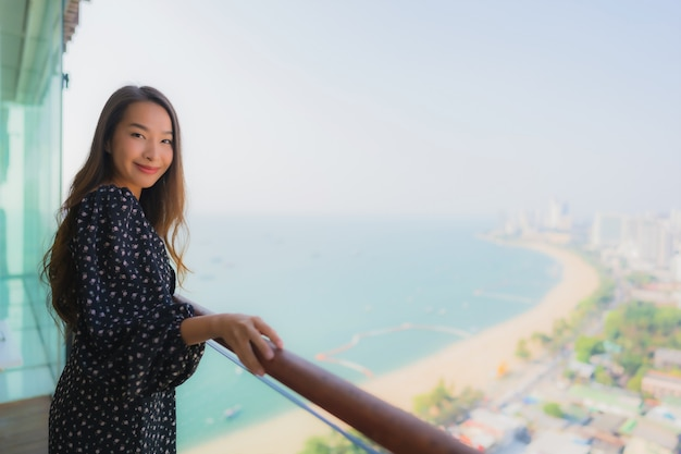 Mooie jonge aziatische vrouw gelukkig lachend op balkon