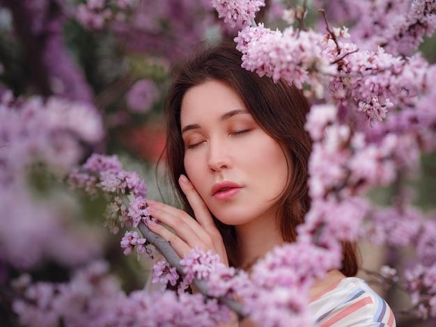 Mooie jonge aziatische vrouw genieten van de bloei van bloemen in het voorjaar. naakt make-up. close-up portret in een viering van lente en bloesem, zoals in japan