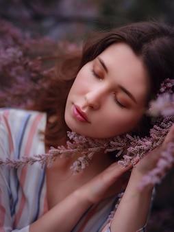 Mooie jonge aziatische vrouw genieten van de bloei van bloemen in het voorjaar. naakt make-up. close-up portret in roze struiken