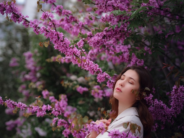 Mooie jonge aziatische vrouw genieten van de bloei van bloemen in het voorjaar. naakt make-up. portret close-up