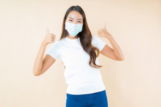 Mooie jonge aziatische vrouw glimlachend en masker dragen ter bescherming van covid19 of coronavirus