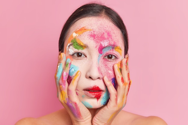 Mooie jonge aziatische vrouw houdt de handen op de wangen heeft kleurrijke verf op het gezicht