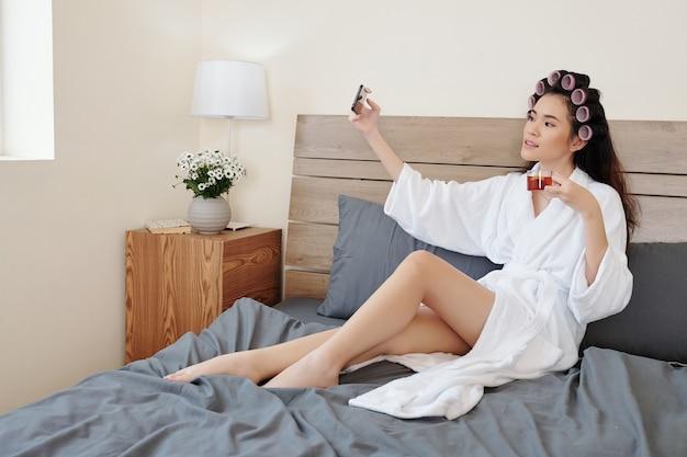 Mooie jonge aziatische vrouw in badjas die selfie neemt met een kopje kruidenthee na het nemen van een bad