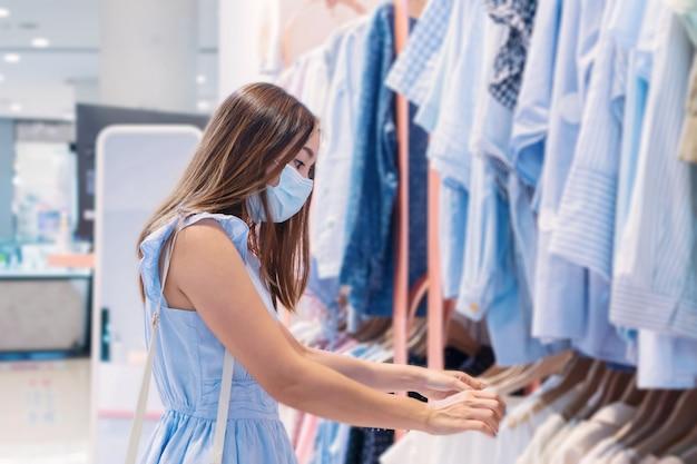 Mooie jonge aziatische vrouw in blauwe jurk en het dragen van beschermend gezichtsmasker mode doeken in warenhuis winkelen