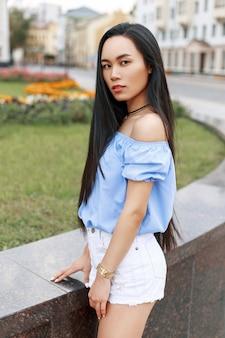 Mooie jonge aziatische vrouw in een blouse en korte broek die in de stad loopt.