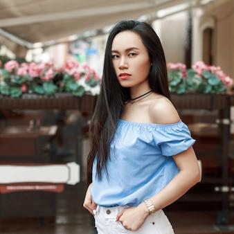 Mooie jonge aziatische vrouw in een stijlvolle blauwe blouse poseren in de buurt van het café