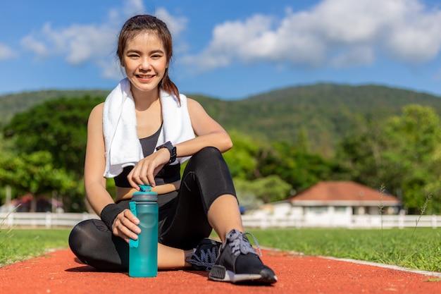 Mooie jonge aziatische vrouw in fitness outfit zittend op renbaan buiten