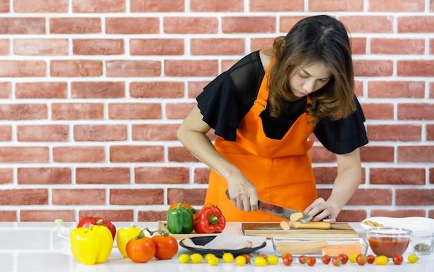 Mooie jonge aziatische vrouw in oranje schort staan voor bruine bakstenen muur van keuken en zorgvuldig snijden hotdog op kooktafel vol verse tomaten, gezonde paprika en gerechten
