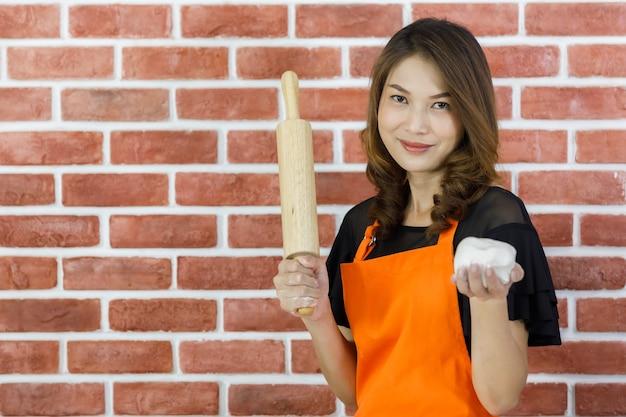 Mooie jonge aziatische vrouw in oranje schort staat glimlachend voor de bakstenen muur van de keuken en tilt deegroller en wit deeg op om te laten zien dat ze klaar zijn om grappig te beginnen met koken van kneden op vakantie