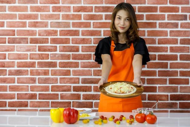 Mooie jonge aziatische vrouw in oranje schort staat voor bruine bakstenen muur in de keuken en geniet van het decoreren van hotdog topping pizza op kooktafel vol verse tomaten en gezonde paprika's