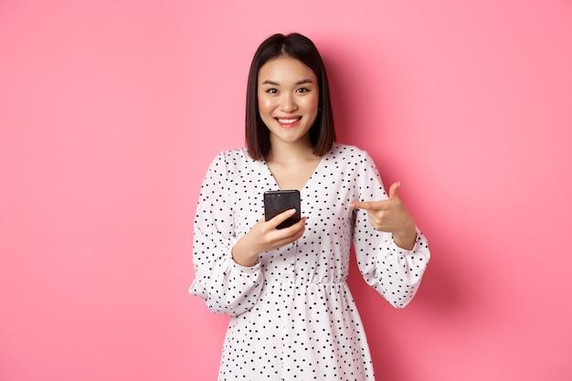 Mooie jonge aziatische vrouw in romantische jurk met behulp van smartphone, glimlachend en wijzend op mobiele telefoon, staande over roze.