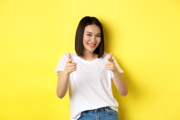 Mooie jonge aziatische vrouw in wit t-shirt, wijzende vingers naar de camera en lachend, prijzend of kies je, zeg gefeliciteerd, staande op gele achtergrond.
