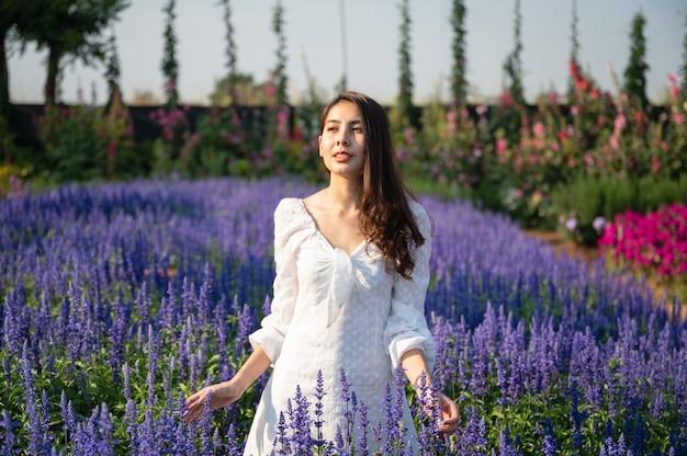 Mooie jonge aziatische vrouw in witte jurk genieten van in lavendelveld op zonnig