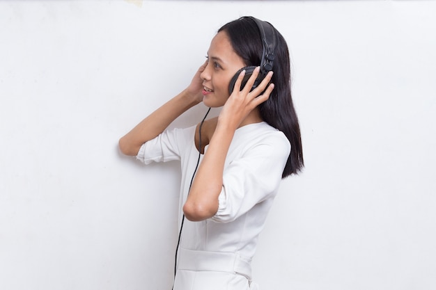 Mooie jonge aziatische vrouw luisteren naar muziek geïsoleerd op een witte achtergrond